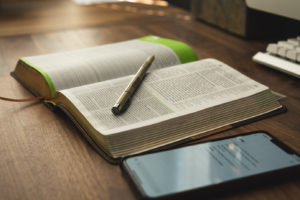 Revered Spurgeon Study Bible with iPhone on Wood Desk